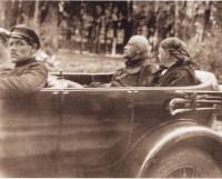 Август 1923 года. Смертельно больной Ленин в Rolls-Royce Silver Ghost на автомобильной прогулке в окрестностях Горок (тогда еще не ленинских). В машине рядом с Лениным сидит Крупская; рядом с шофером - начальник охраны Ленина Покалн.